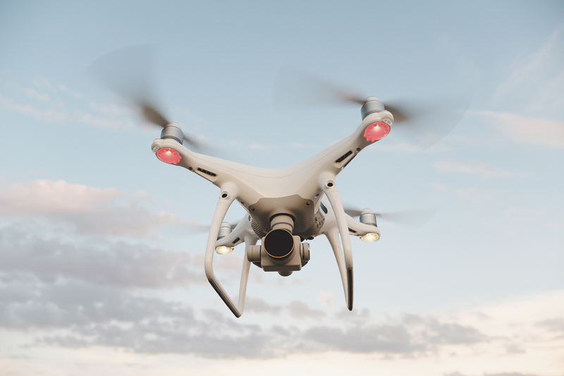 White drone hovering in a bright blue sky. Drone copter flying with digital camera